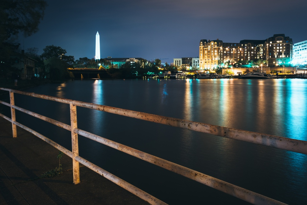 The Washington Monument and buildings along the waterfront at night in Washington, DC.