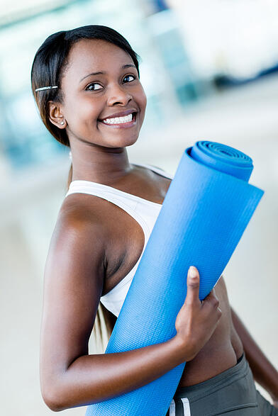 Fit woman at the gym holding yoga mat